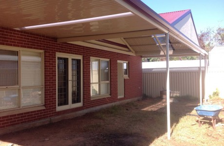 Flat outback verandah with central gable section sheeted with corrugated iron
